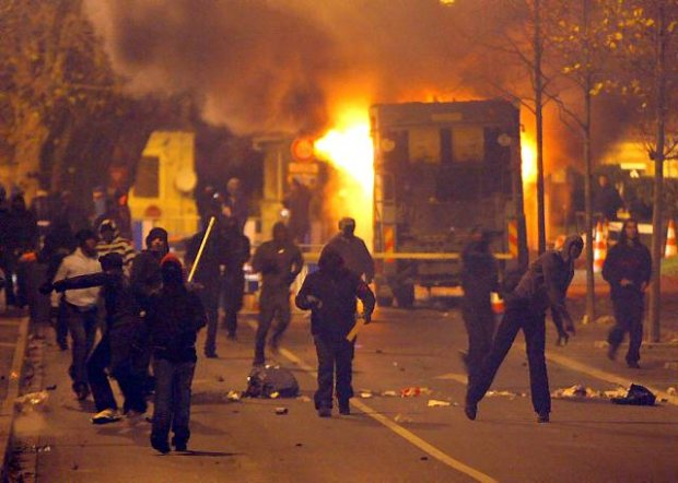 Young residents of Villiers-le-Bel, a northern Paris suburb, throw stones at riot police (unseen) while a garbage truck burns in the background during clashes late Monday, Nov. 26, 2007. Rampaging youths threw Molotov cocktails and set fire to cars in a troubled neighborhood outside Paris on Monday, the second night of street violence after two local teens were killed in a crash with a police patrol car. (AP Photo/Thibault Camus)