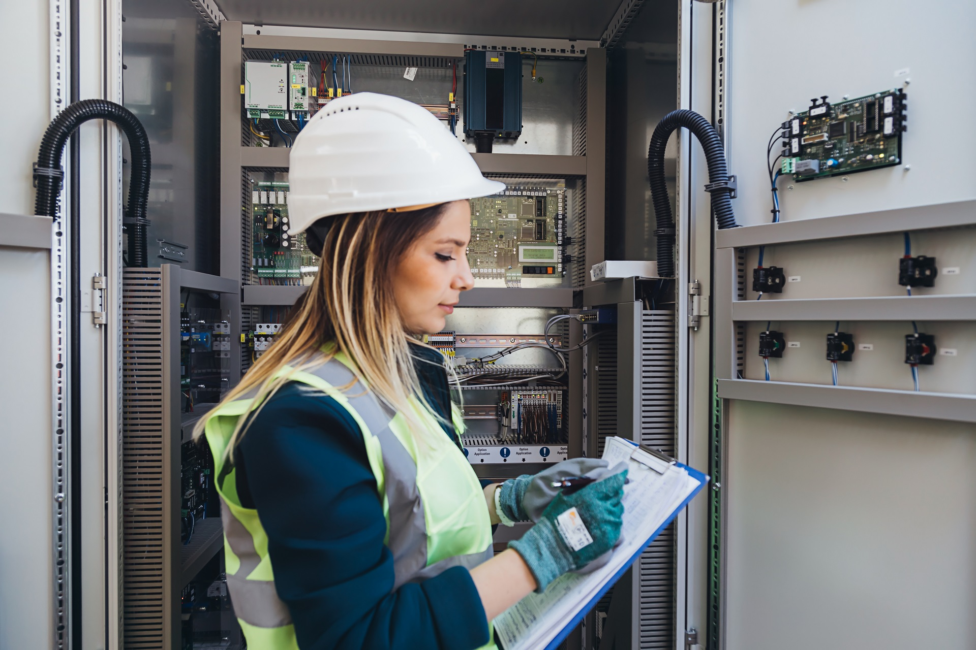 Young woman industrial service engineer wearing white worker headwear standing, working, checking conducts a safety check front of a control panel read and writing notes about technical problems in boiler energy control room of modern thermal or nuclear power plant electric energy station. xxxl size taken with canon 5d mIV