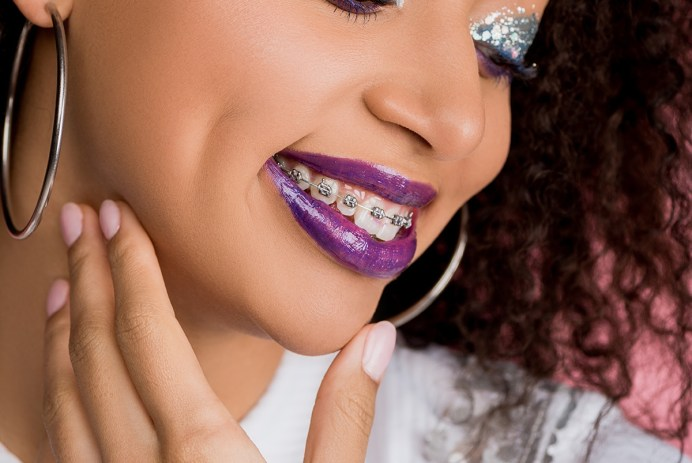 cheerful african american girl with silver glitter eyeshadows and purple lips wearing paillettes dress, isolated on pink