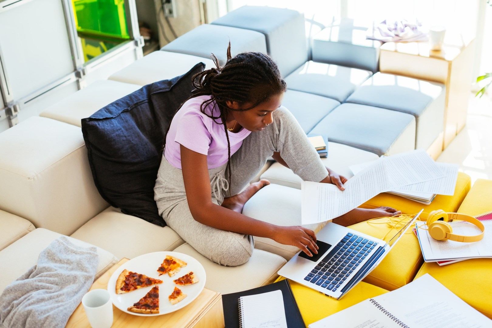 Black teen girl studying at home with her laptop and pizza