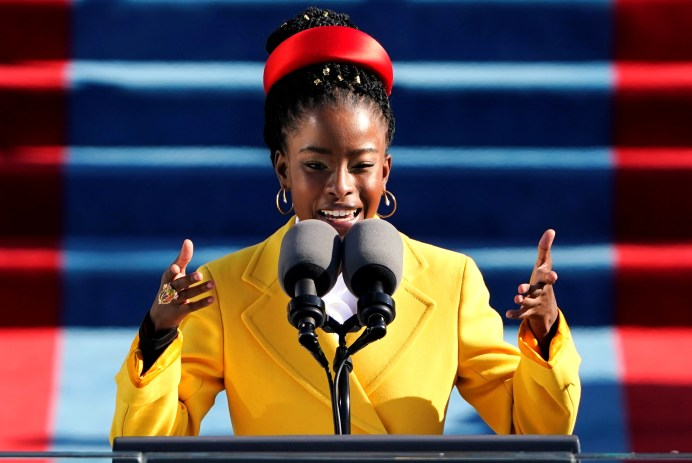 amanda gorman wearing yellow coat and red headband delivering inaugural poem at podium