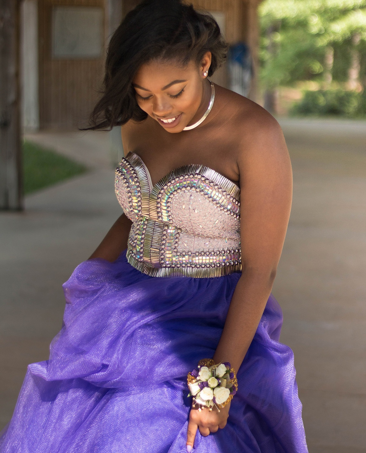 black girl wearing prom dress with beaded bodice and purple tulle skirt