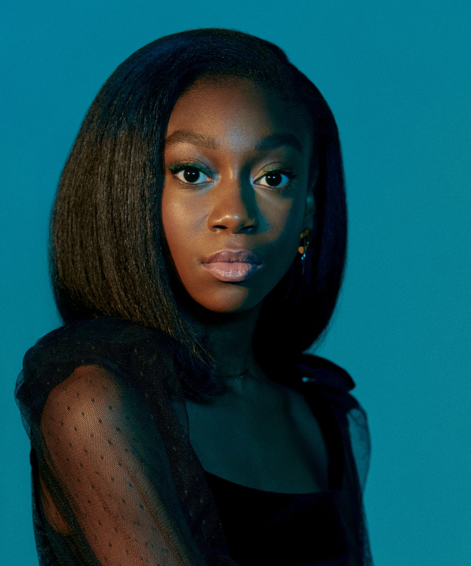 Shahadi Wright Joseph wearing black top with sheer sleeves against blue background