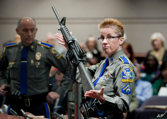 FILE - A firearms training unit detective holds up a Bushmaster AR-15 rifle, the same make and model of gun used in the Sandy Hook School shooting, during a hearing on gun laws in Hartford, Conn., Jan. 28, 2013.