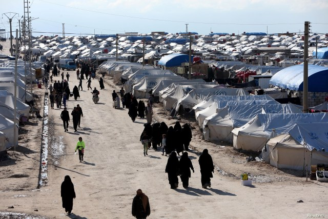 FILE - Women walk through al-Hol displacement camp in Hasaka governorate, Syria, April 1, 2019.