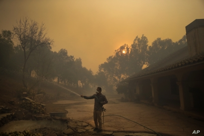 Marco Alcaraz uses a garden hose to protect his girlfriend's home as the Easy fire approaches Wednesday, Oct. 30, 2019, in Simi…