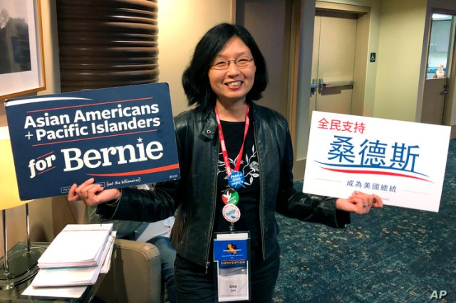 Una Lee Jost, a lawyer from Pasadena, Calif., holds signs supporting Bernie Sanders at the California Democratic Convention in…
