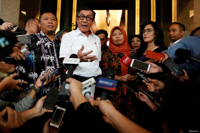 Indonesia's Law and Human Rights Minister Yasonna Laoly talks to journalists with Baiq Nuril Maknun, a school bookkeeper who was jailed after she tried to report sexual harassment, in Jakarta, Indonesia, July 8, 2019.
