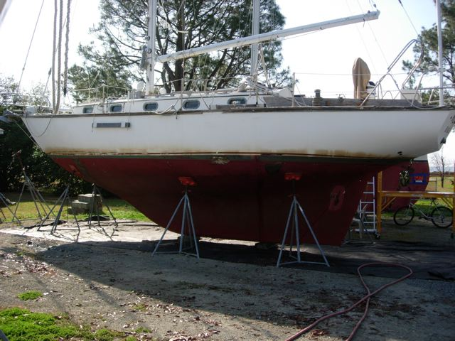 Picture of a boat with a cutaway keel. There is a concave shape in the profile up forward, with the keel really beginning under where the second cabin porthole is. The rudder is attached to the trailing edge of the keel, offering some protection and making it less likely to snag lines and other debris.