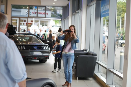 A lady taking a photo inside a car showroom