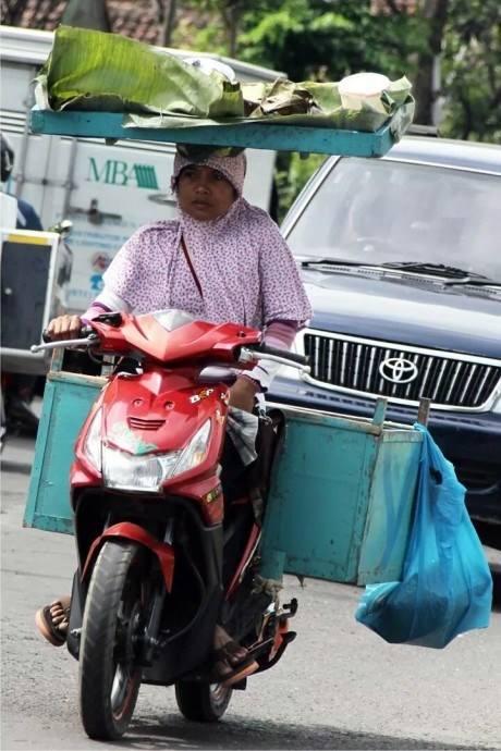 wpid-ibu-mengendarai-motor-sambil-menahan-tempeh-di-kepala-.jpg.jpeg