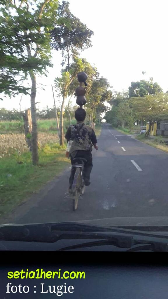 Gokil....pria asal Blora ini bawa 3 kendi dikepala sambil naik sepeda di jalan raya