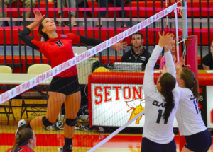 Junior outside hitter and captain, #11, Cassie Hausfield delivers a powerful spike. Photo courtesy of D.Clark/Setonian