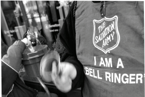 Salvation Army red kettle and bell ringer stands outside of Chicago store in the 2014 season. Photo courtesy by salarmychicago.org