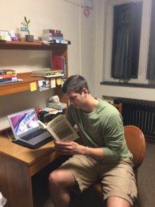 Noah Davis sits and reads Selected & New Poems by Jim Harrison in his dorm. Davis normally reads at night before he rests his eyes.
