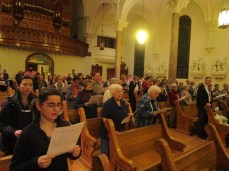 """Members of the service stand to sing the concluding hymn, """"Let There Be Peace on Earth."""" Photo by C.Arida/Setonian."""