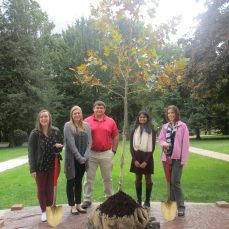 From left: Biology Club officers Hannah Hartman, Abby Gillis, Nate Zanoni and Shreya Sudadi and club advisor Jessica Bryzski smile for a photo with the tree dedicated to Suzanne Rogers on Oct. 12.