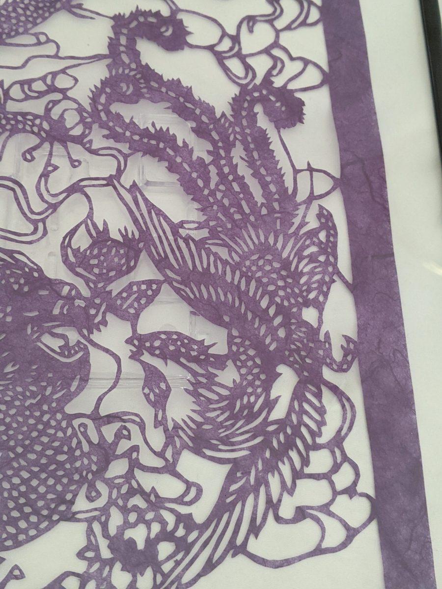 Cut paper dragon in purple, detail