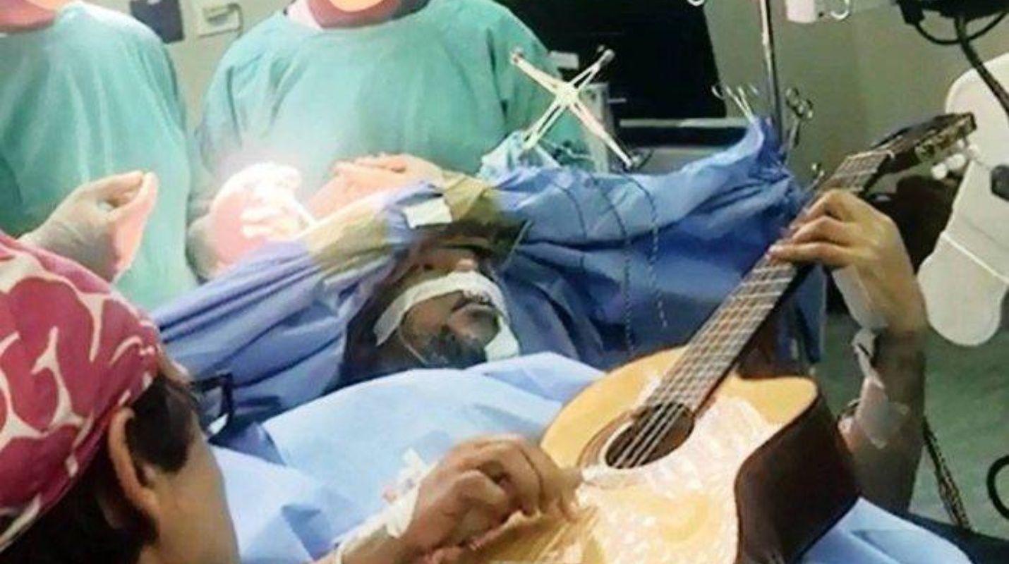 Mientras lo operan músico toca la guitarra