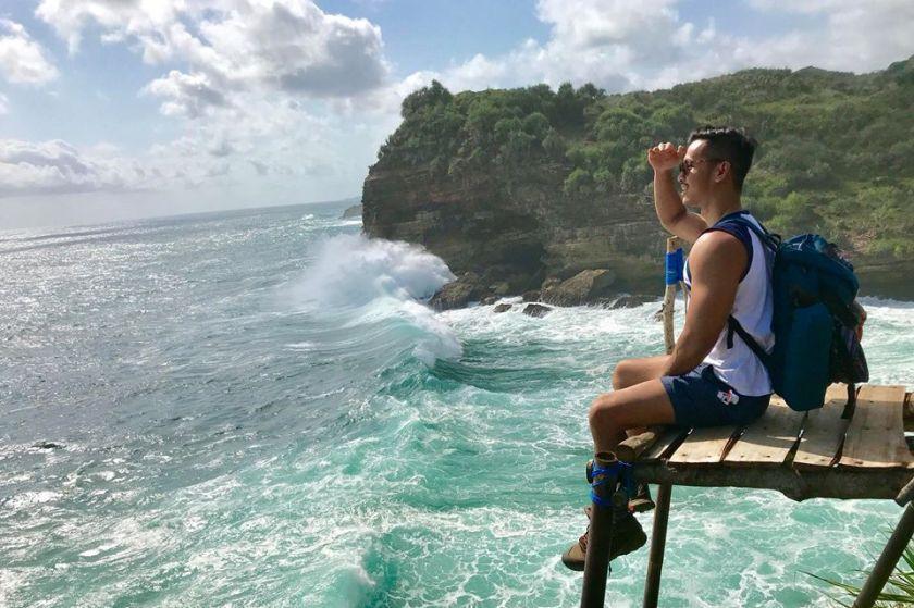 Em Surasak travel blogger for sevenseas media sits at the ocean edge