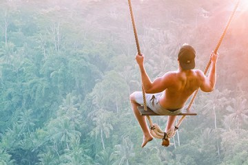 man on a swing in bali