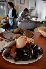Curanto is a pulse-raising platter of giant mussels, clams, smoked pork, chorizo, chicken, potato, and two types of 'milcao' (dense potato cake). Chiloe, Chile