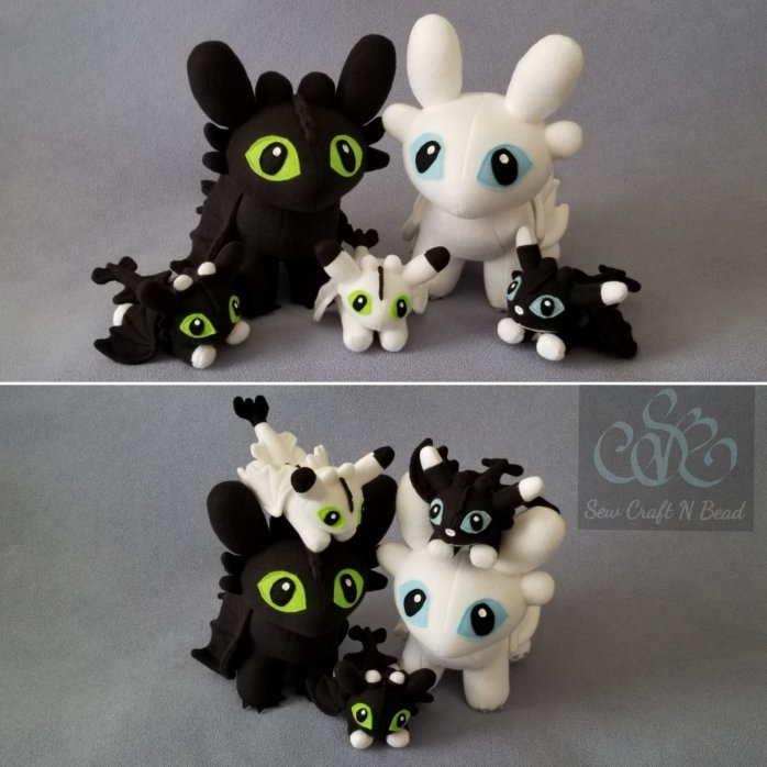 Standing Night and Light Fury plush dragons with the Night Light Fury Baby plush dragons.