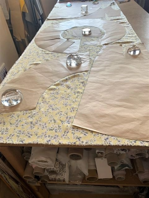 Cutting table with yellow viscose fabric and patterns layed on top of it ready for cutting a viscose floaty dress