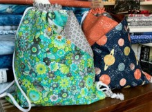 Here is a great FREE video showing you how to make this easy and fun drawstring bag with front pockets you can customize with different fabrics and buttons.