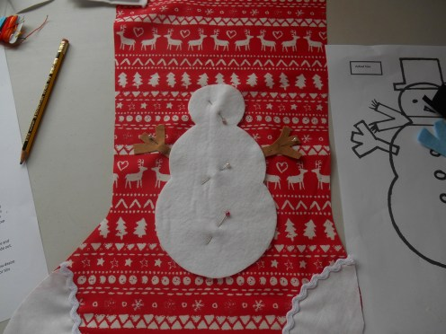 Pin snowman on right side and tuck arms under the body a little