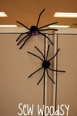 Two pipe cleaner spiders on a magnetic wall.