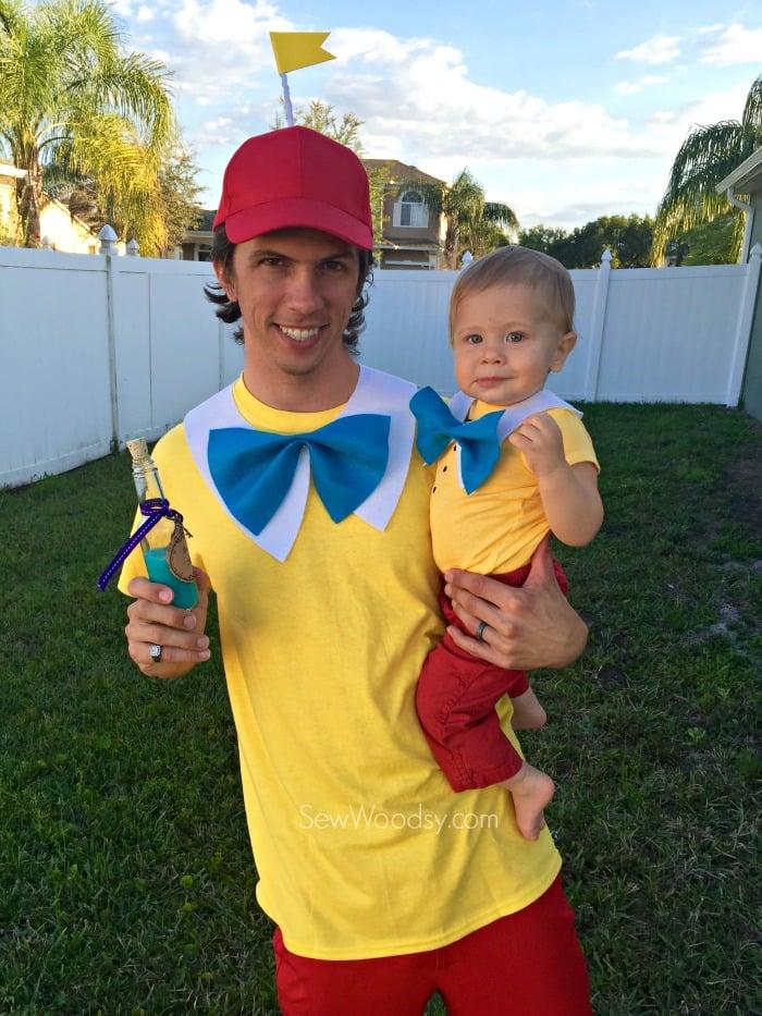 Man holding a baby, both dressed as Tweedledum and Tweedledee.