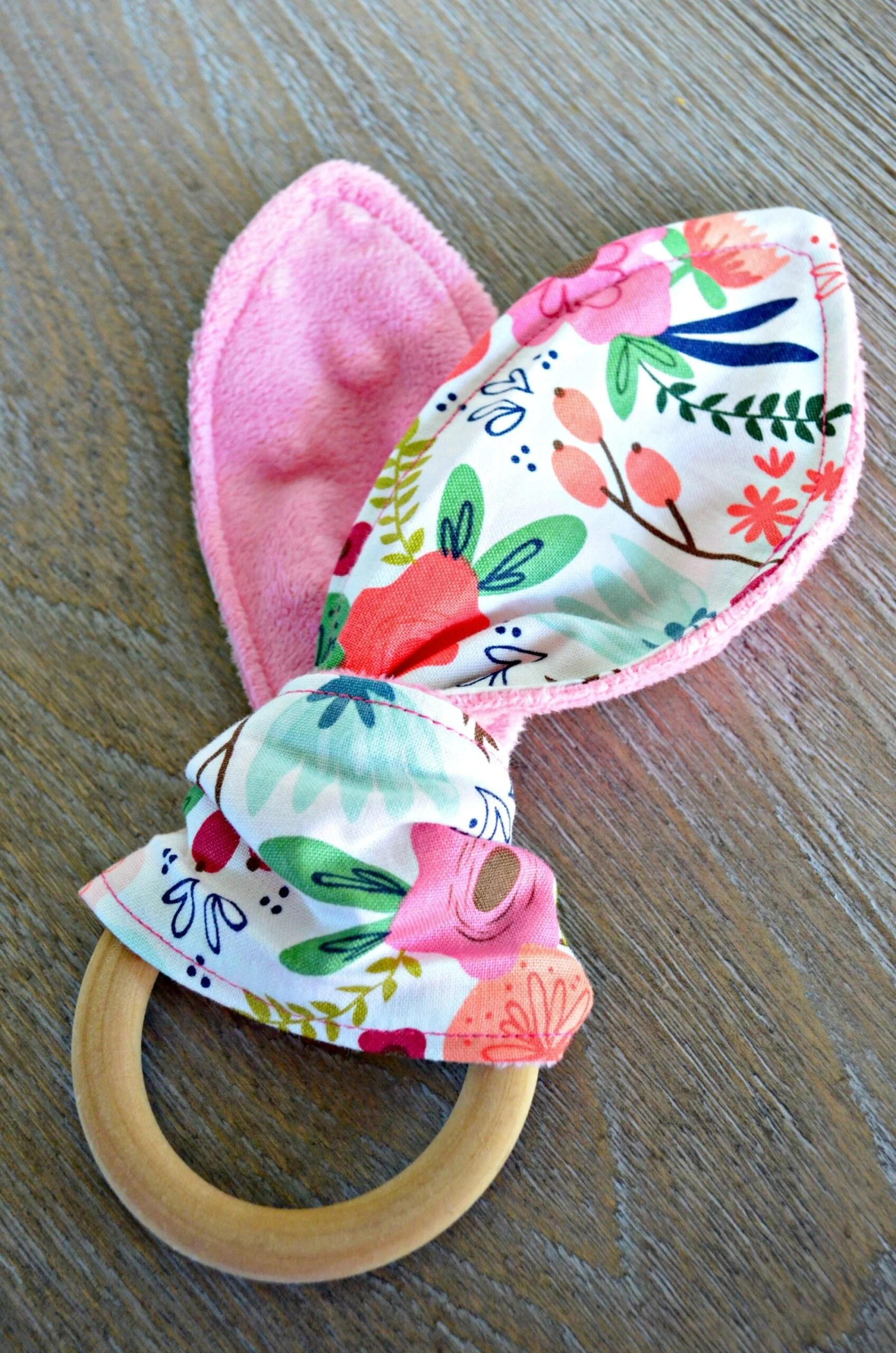 Wooden teething ring with pink and floral fabric tied around it.