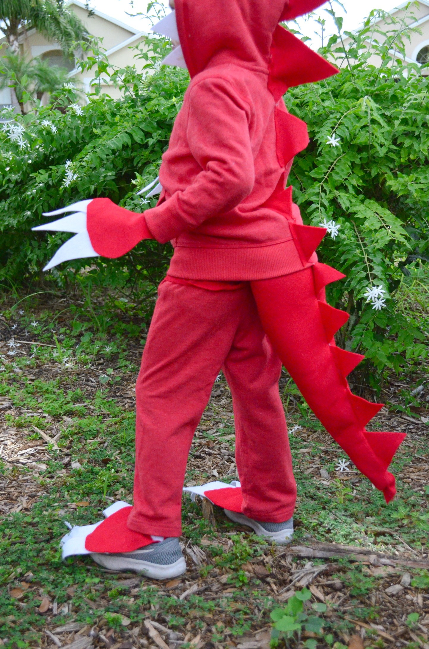 Side profile of a little boy in a red handmade dinosaur costume with claws and tail.