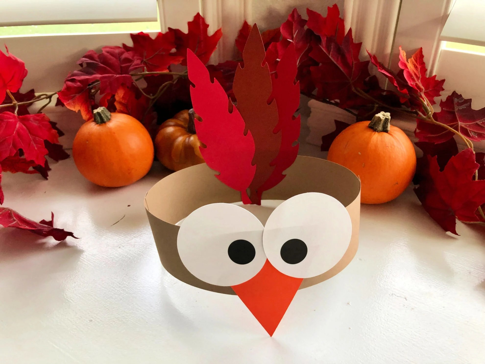Turkey Paper Headband with fall leaves in the background.