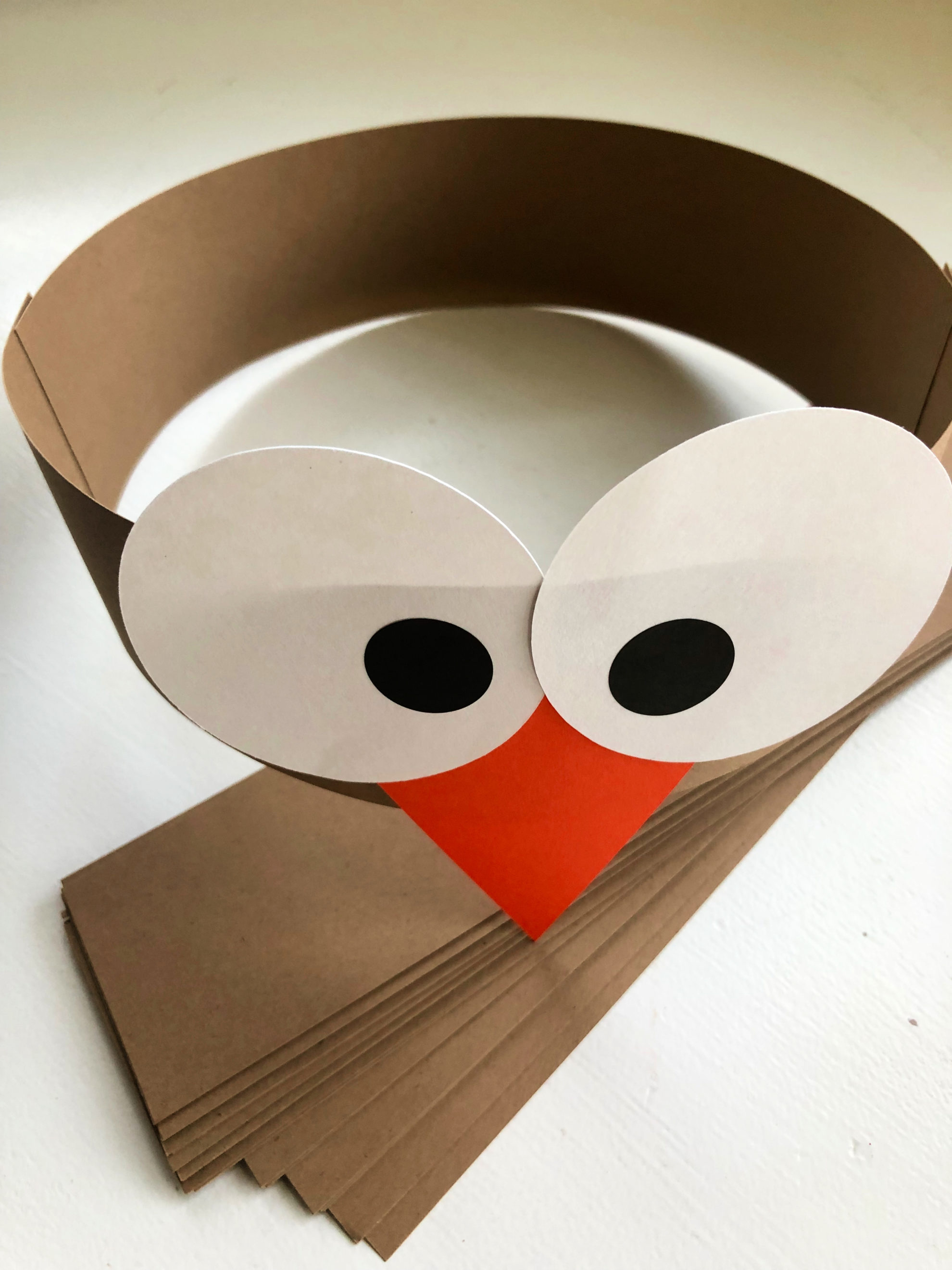 Brown paper headband with white circle and black pupil stickers with an orange triangle beak.