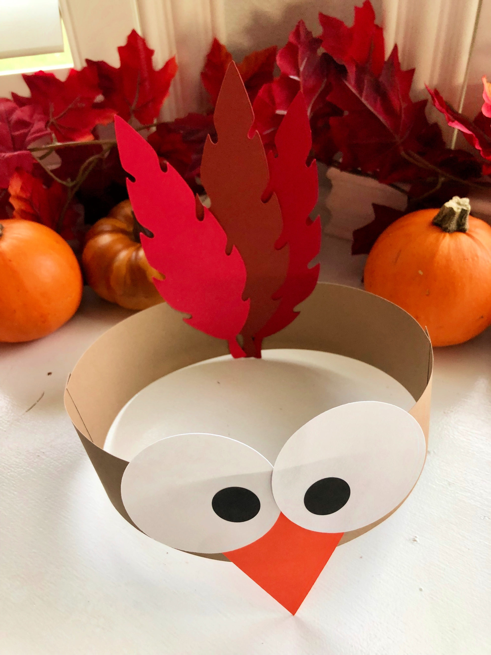 Top view of a turkey paper headband with fall leaves in the background.