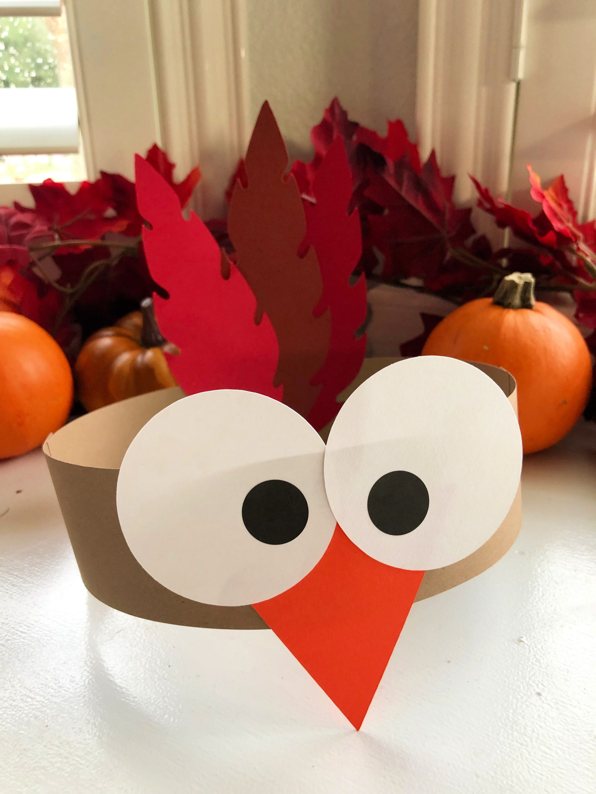 Turkey Paper Headbands for Kids with fall leaves and pumpkins in the background.