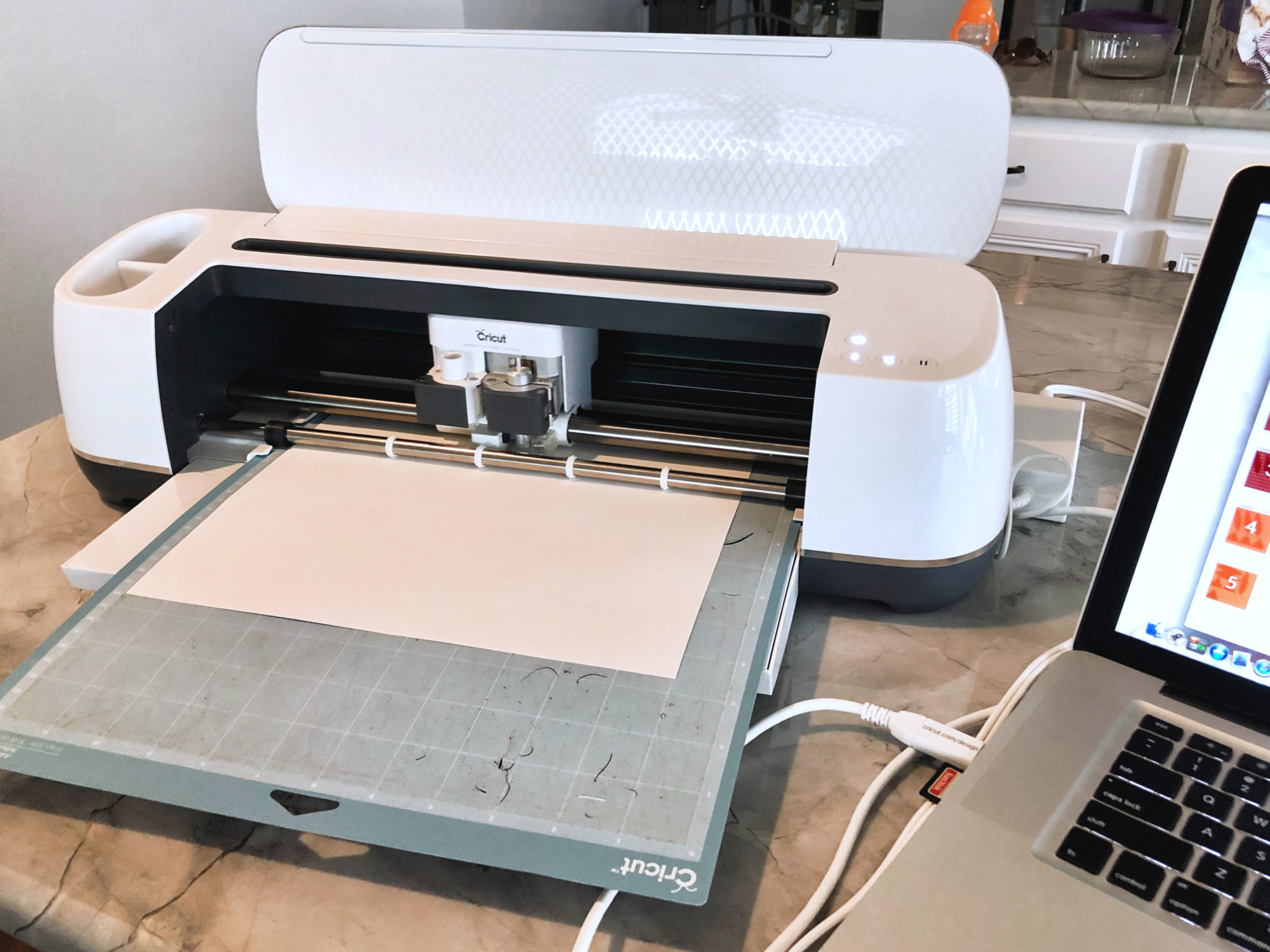 Cricut Maker loaded with white cardstock sitting on a marble countertop.