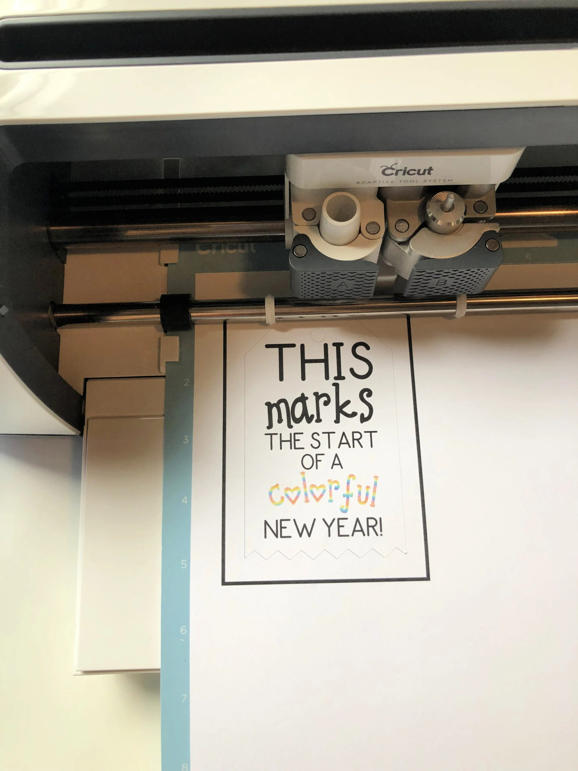 Top view of a Cricut Maker Machine cutting out a paper on a blue mat.