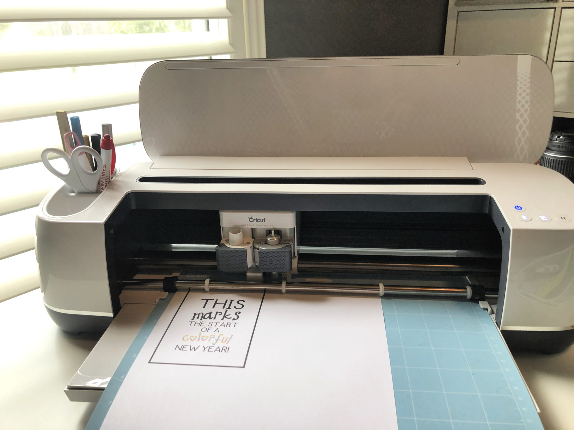 Cricut Maker with blue mat loaded and paper with printed design on paper.