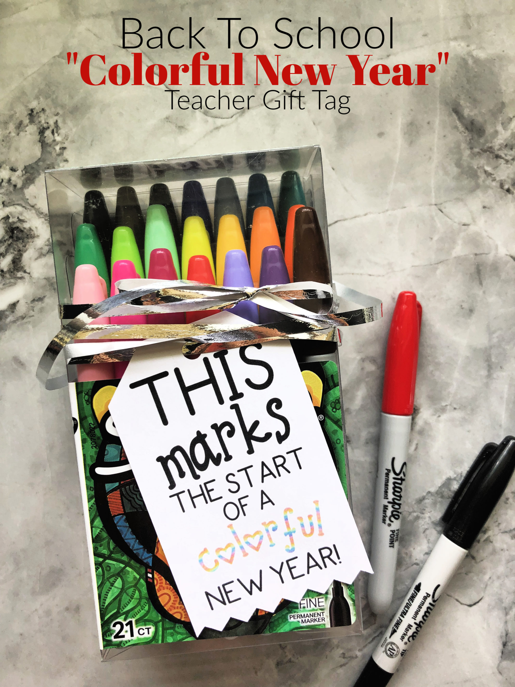 Box of Sharpie markers with a gift tag on it resting on marble countertop with text on image.