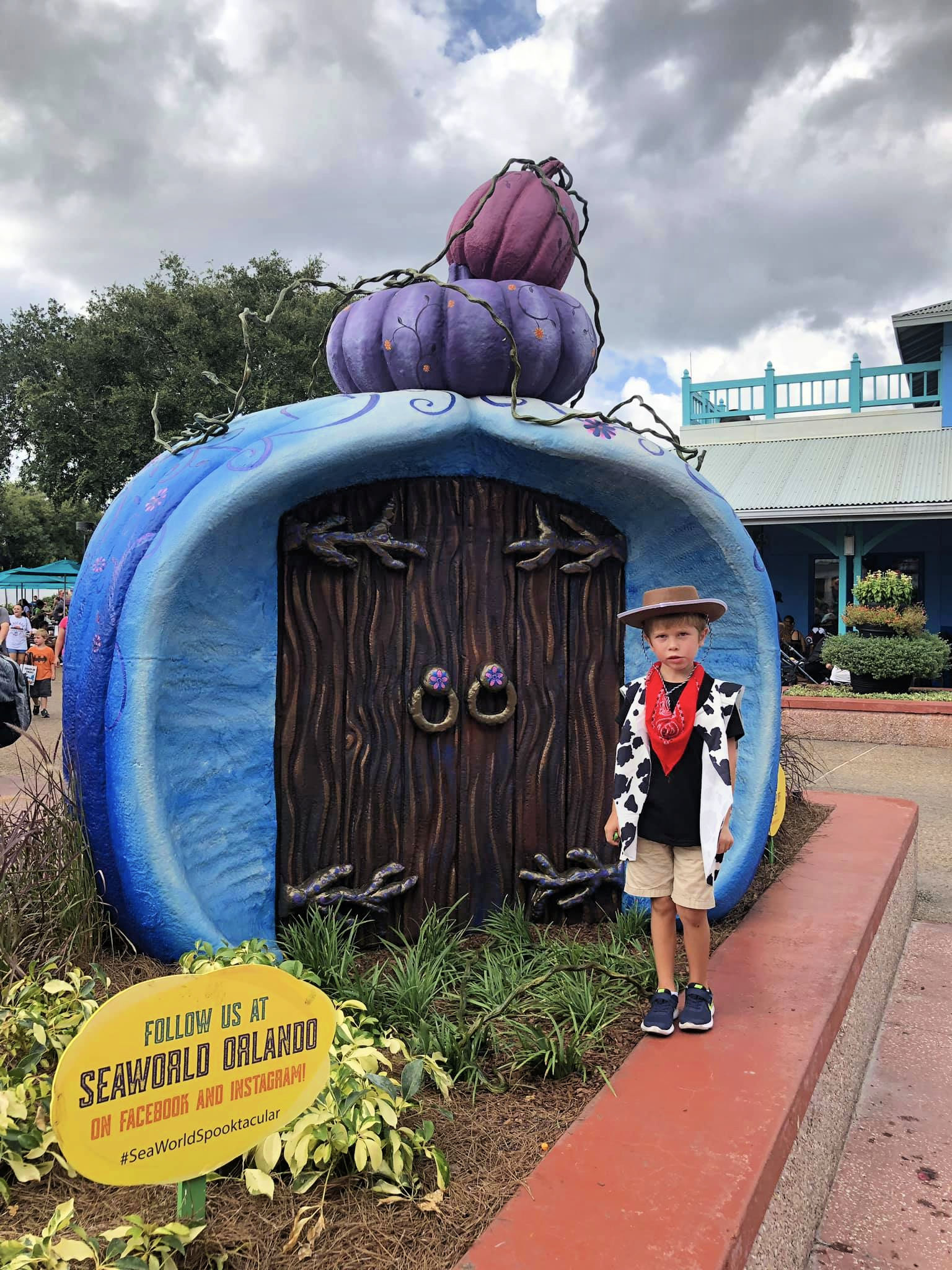 Little boy dressed as a cowboy infront of Halloween decor at SeaWorld.