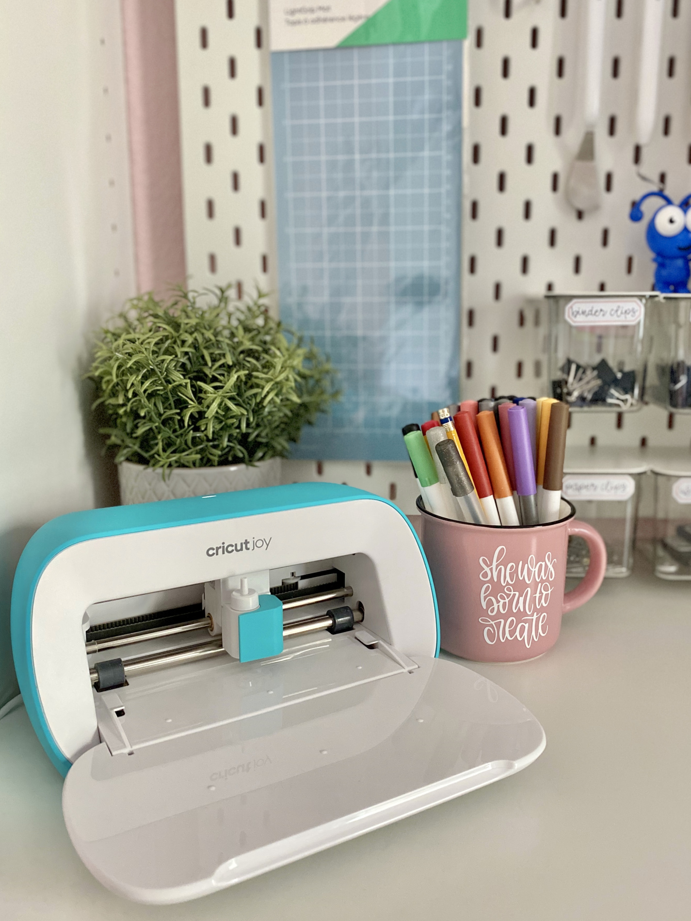 Cricut Joy with peg board in background with Cricut blue mat and pink cup.