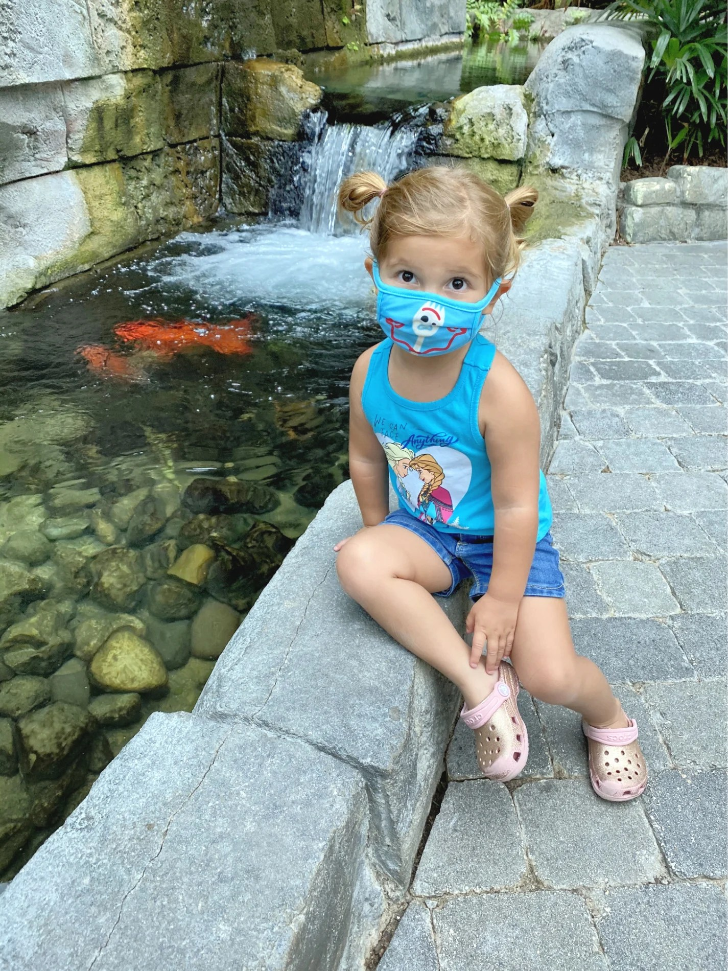 Little girl with blue mask on face sitting next to a koi pond.