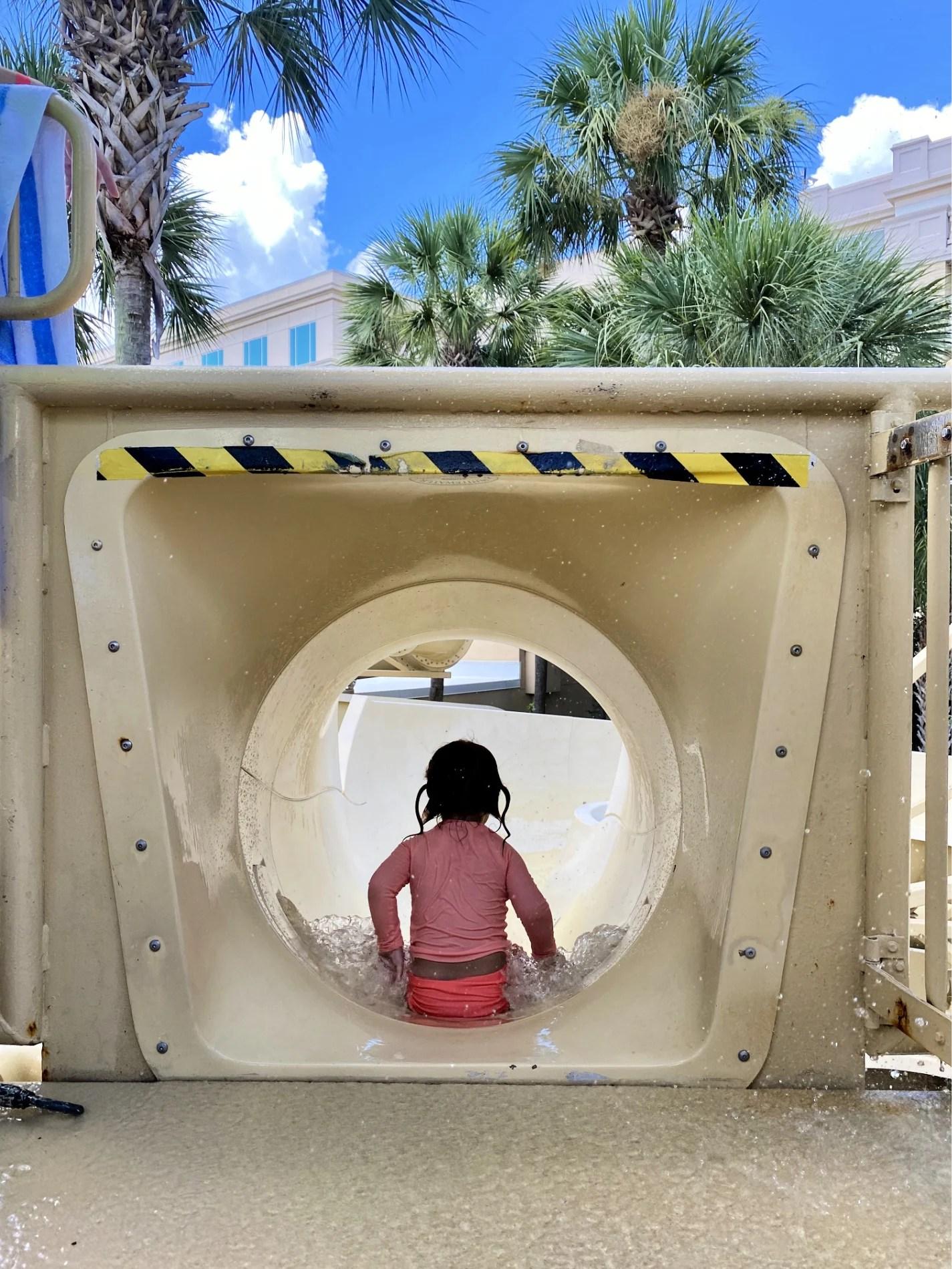 Little girl sliding down on her bottom on a water slide.