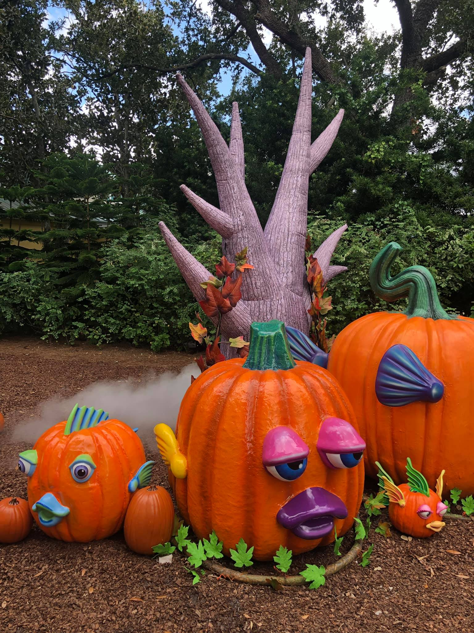 Three decorated fake pumpkin with a blow up tree and fog in the background.