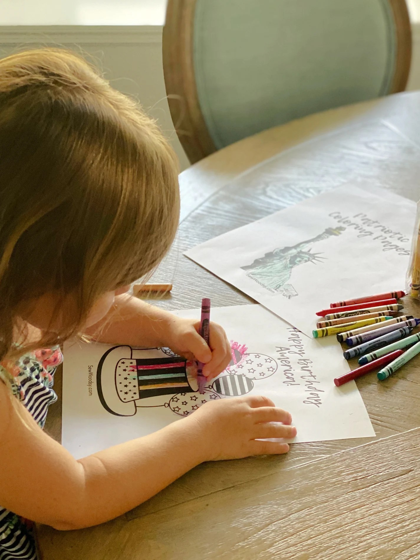 Little girl coloring at a wood table with crayons.