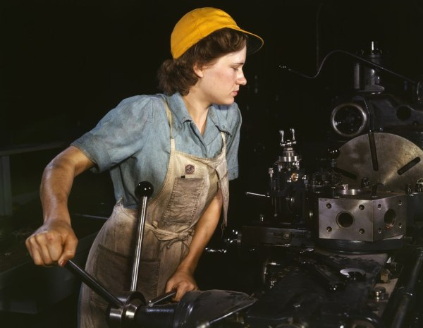 Image of a woman in overalls and cap working in a factory
