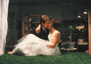 An image from Secretary showing Lee is wearing a wedding dress and being held by Mr Grey as he lays her down on a box covered in astroturf